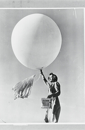 Black and white photo of a woman holding a weather balloon