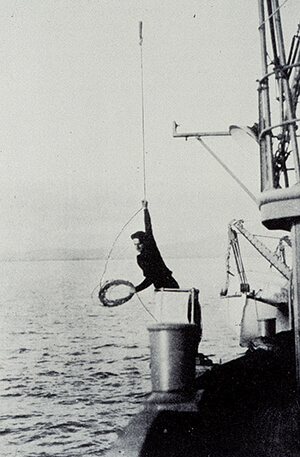 Black and white photo of a sailor holding a rope