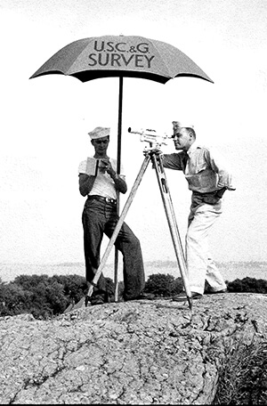 Black and white photo two men surveying under an umbrella